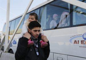 幼い妹を方に乗せ、ロシア人を乗せたバスの脇を行き過ぎるシリア人の男性。彼等もダマスカスから逃れてきた避難民である。