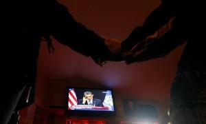 手を取り合ってオバマ大統領の演説に聴き入る人々